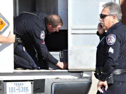 Officer Dylan Hale, center, secures an explosives transport box containing military-grade explosives to the back of a vehicle on December 31 at the Midland International Airport in Texas.