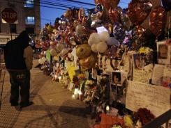A person stops at a memorial to Whitney Houston outside New Hope Baptist Church in Newark, N.J., early Saturday.