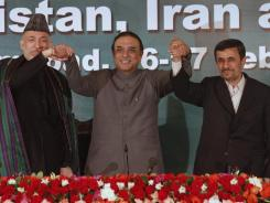 Pakistan's President Asif Ali Zardari, center, holds hands with Afghan President Hamid Karzai, left, and Iranian President Mahmoud Ahmadinejad after Friday's news conference in Islamabad, Pakistan.