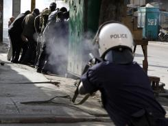A police officer fires tear gas at close range directly into a group of anti-government protesters sheltering behind a kiosk on Saturday, in Dakar, Senegal.