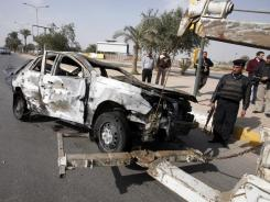 Security forces prepare to tow away a destroyed car after a car bomb attack in Baghdad on Sunday.