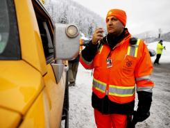 Ajai Sehgal, with King County Search and Rescue, works at a staging area near Stevens Pass ski resort in Skykomish, Wash., near where three skiers were killed in an avalanche on Sunday.