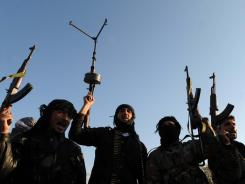 Members of the Free Syrian Army raise their weapons during a patrol Saturday in Idlib in northwestern Syria.