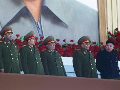 New North Korean leader Kim Jong Un, far right, looks down the line at military leaders at Kumsusan Memorial Palace in Pyongyang on Thursday. His nation threatened South Korea over military drills.