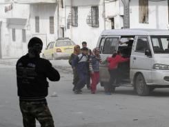 Fleeing:  Syrians leave Idlib on Tuesday after tanks roll in.