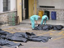 Forensic workers zip open a body bag at the morgue in Tegucigalpa, Honduras, on Monday, continuing to identify prison inmates that died in last week's deadly prison fire.