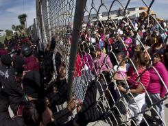 Police hold back relatives of inmates outside the Apodaca prison in Mexico on Sunday. A fight among inmates led to a riot that killed dozens of prisoners.