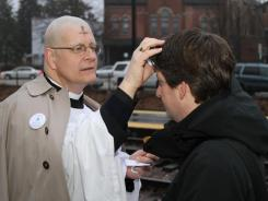 The Rev. Scott Elliott, a deacon in the Episcopal Diocese of Chicago, takes the sign of Lent to the public on Ash Wednesday in 2011.