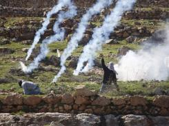 A Palestinian hurls stones at Israeli troops Tuesday outside a prison near Ramallah. Palestinians demonstrated in solidarity with prisoner Khader Adnan.