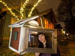 Jenna Hansen with her birdhouse library in her front yard in Madison, Wis.