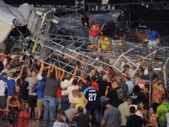 Fans waiting to see Sugarland help each other after high winds blew a stage over at the Indiana State Fair in Indianapolis on Aug. 13.