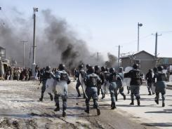 Afghan policemen run toward protesters during an anti-U.S. demonstration Wednesday in Kabul, Afghanistan.