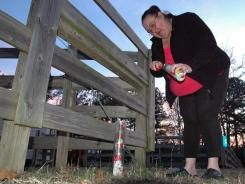 Gail Denny places a candle and stuffed animal outside the home of Savannah Hardin near Attalla, Ala.