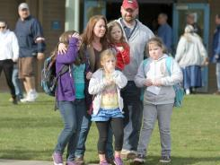 Parents and children leave Armin Jahr Elementary School on Wednesday in Bremerton, Wash.