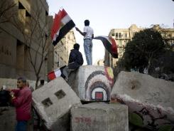 A year after overthrowing the Mubarak regime: Men sell Egyptian flags this month atop a torn down wall that the military had built to contain the protesters in Cairo's Tahrir Square.