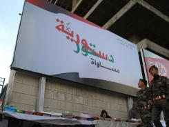 "Syrian soldiers walk past a billboard that says in Arabic ""Syria Constitution -- equality"" Thursday in Damascus. Syrian opposition groups rejected a newly proposed constitution."