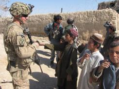 A soldier talks to children in the southern Afghan village of Nalgham, where residents who fled during Taliban rule have returned after a security crackdown.