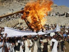 Afghans burn an effigy representing President Obama during Friday's protest over Quran burning at a U.S. military base in Afghanistan, in Ghani Khail, east of Kabul.