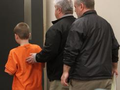 The 9-year-old boy accused of accidentally shooting a classmate at a Bremerton, Wash., elementary school is led away after his juvenile detention hearing in Kitsap County, Wash.