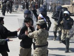 An Afghan police officer attempts to calm down a protester during an anti-U.S. demonstration in Kunduz.
