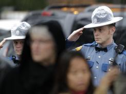 Two Washington State Patrol troopers salute as a procession of law-enforcement vehicles, bearing the body of slain WSP trooper Tony Radulescu, makes its way to the funeral home.
