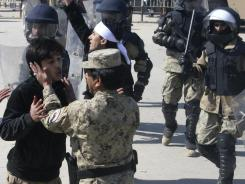 An Afghan officer tries to calm down a protestor on Saturday during manifestations against the burning of Qurans in a U.S. base north of Kabul.