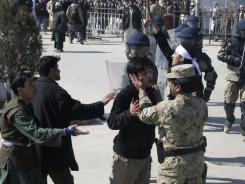 An Afghan police officer calms down a protestor during an anti-U.S. demonstration in Kunduz, Afghanistan, on Saturday.
