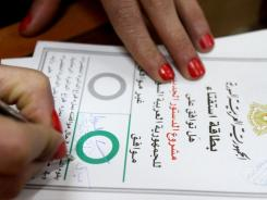 "A Syrian woman checks ""Agree"" on a ballot card and adds ""Definitely yes for a democratic Syria"" before casting her vote on a new constitution in Damascus."