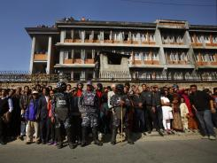 Nepalese policemen stand guard as locals look on near the site of the explosion in Katmandu, Nepal, on Monday.