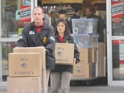 DEA Special Agents David Melenkevitz and Mia Ro remove boxes of prescription painkillers and other evidence from a CVS store Feb. 4 in Sanford, Fla.