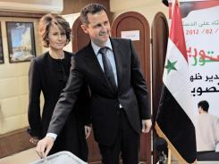 This handout picture released by the Syrian Arab News Agency shows President Bashar al-Assad casting his ballot Saturday as his wife, Asma, looks on.