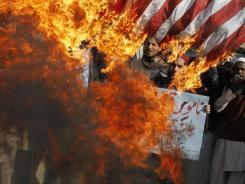 Pakistani protesters in Lahore burn representations of U.S. flags to condemn the reported burning of Qurans in Afghanistan by U.S. troops.