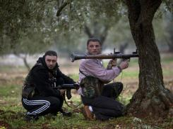 Free Syrian Army fighters take positions Monday as government troops advance toward Sarmin, in north Syria.