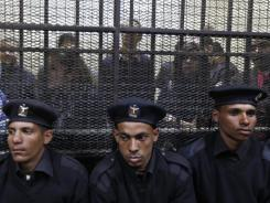 Policemen sit in front of Egyptian employees of pro-democracy groups during their trial Sunday in Cairo.