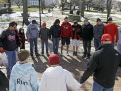 Students and parents pray for victims of the Chardon High School shooting on the square in Chardon, Ohio, on Tuesday.