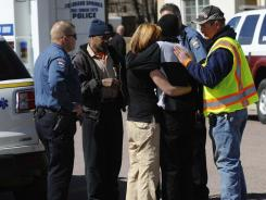 Employees are comforted after being released from a hostage situation Tuesday inside the Urological Associates office in Colorado Springs, Colo.