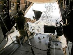Marine Corps Cpl. William Aider releases a batch of leaflets April 3 while aboard an aircraft flying over Afghanistan.