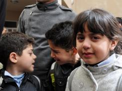 Students cry in a schoolyard after the fatal shooting of an American teacher Thursday at a school in Sulaimaniyah, Iraq.