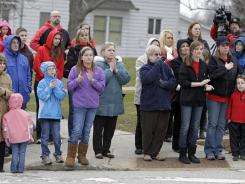 Residents of Chardon, Ohio, applaud as hundreds of students and parents march to the high school Thursday to honor the three students who were killed in a shooting there Monday.