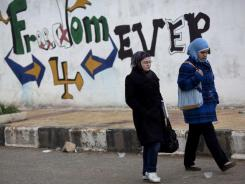 "Women walk past graffiti Thursday that reads ""Freedom 4 EVER"" on the outskirts of Idlib, north Syria."