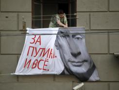 A Russian woman tries to remove an election poster from the wall of an apartment house in downtown Moscow on Friday.