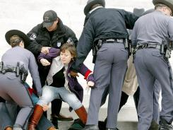 Protesters are removed from the front steps of the Virginia Capitol on Saturday.