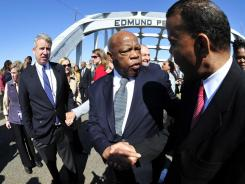 Rep. John Lewis, D-Ga., center, crosses the Edmund Pettus Bridge on Sunday.