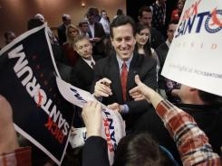 Republican presidential candidate Sen. Rick Santorum, center, shakes hands during a campaign rally Saturday.