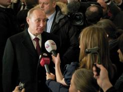 Russian Prime Minister and presidential candidate Vladimir Putin talks to the media at a polling station in Moscow on Sunday.