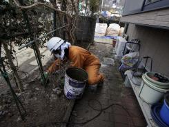 A worker scoops up a layer of radiation-contaminated soil and ice in the garden of a private home in Fukushima, Japan, on Feb. 21.