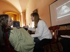 Registered nurse Julie Aber, right, administers an ultrasound to Erin Glockner last year in Columbus, Ohio.