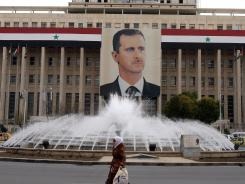 A woman walks past a banner of President Bashar Assad hanging from a central bank building Feb. 28 in Damascus, Syria.