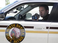 North Dakota State Trooper Jamey Jahner measures the speed of vehicles with a laser gun on Interstate 29 in Fargo.