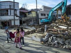 Children walk home from school Wednesday as workers sort through the rubble of a house damaged during last year's tsunami in Kesennuma, Japan.